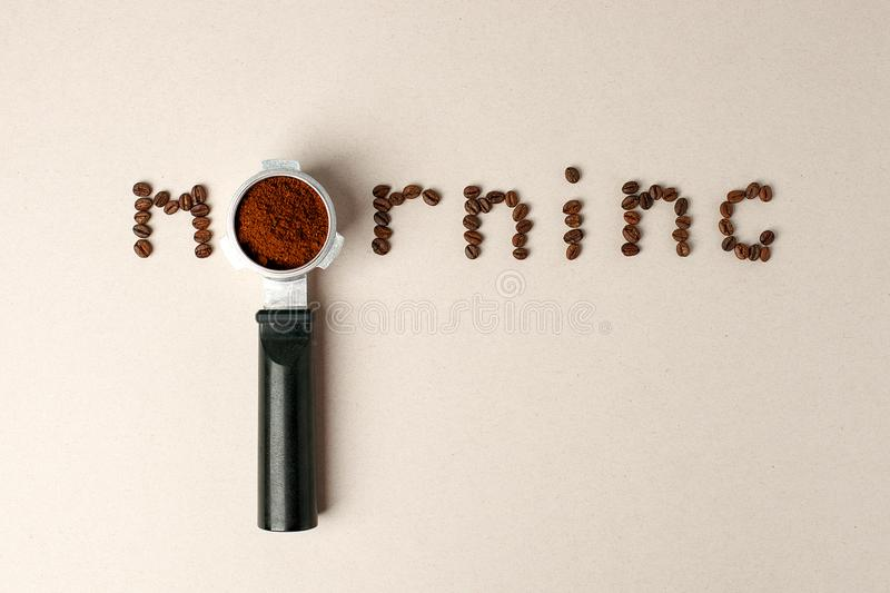 Espresso coffee machine handle on and coffee beans word morning on gray background, minimal concept stock images