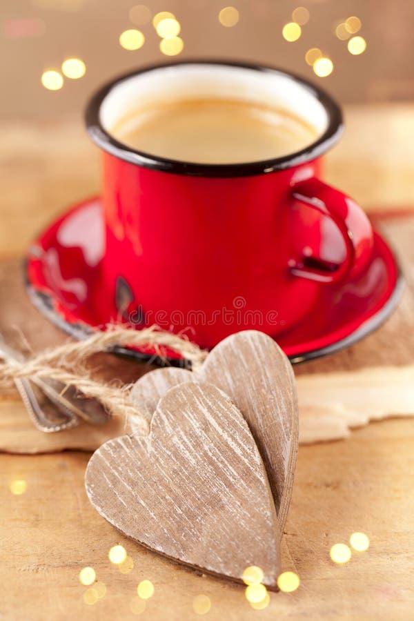 Espresso coffee, red enamel mug, two hearts. Espresso coffee, red enamel mug, two wooden hearts and festive lights, shallow dof royalty free stock photos