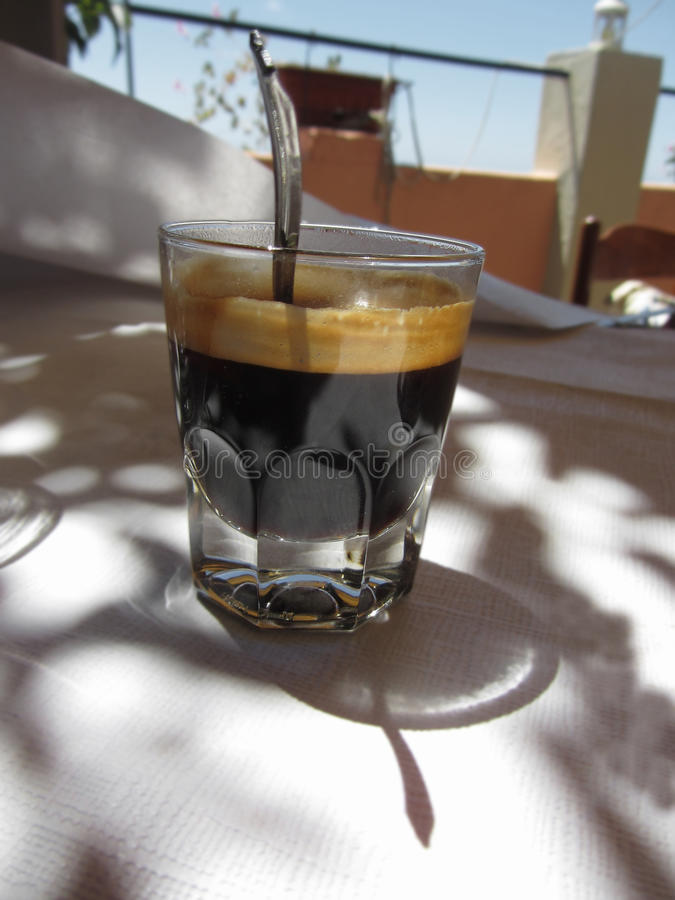 Espresso coffee with rum, sugar and lemon rind in a shot glass. Typical recipe of Livorno, Italy stock photos