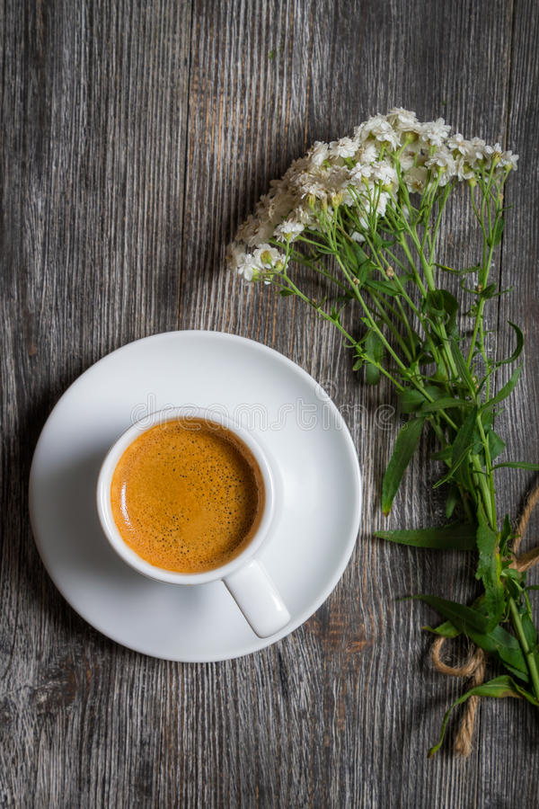 Espresso coffee and a small bouquet of flowers royalty free stock image