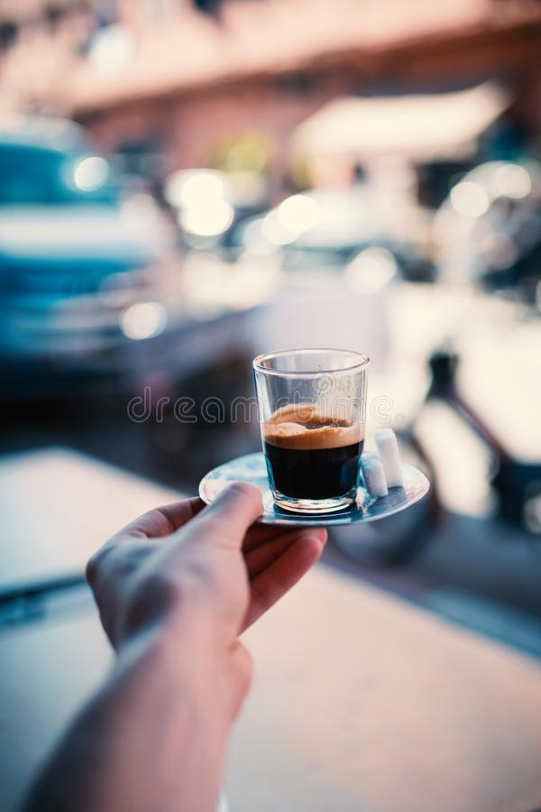Espresso coffee on the street in Marrakech - Morocco. Man holding a cup of fresh brewed coffe on a iron plate with sugar. stock image