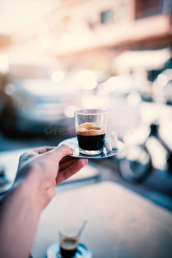 Espresso coffee on the street in Marrakech - Morocco. Man holding a cup of fresh brewed coffe on a iron plate with sugar. royalty free stock images