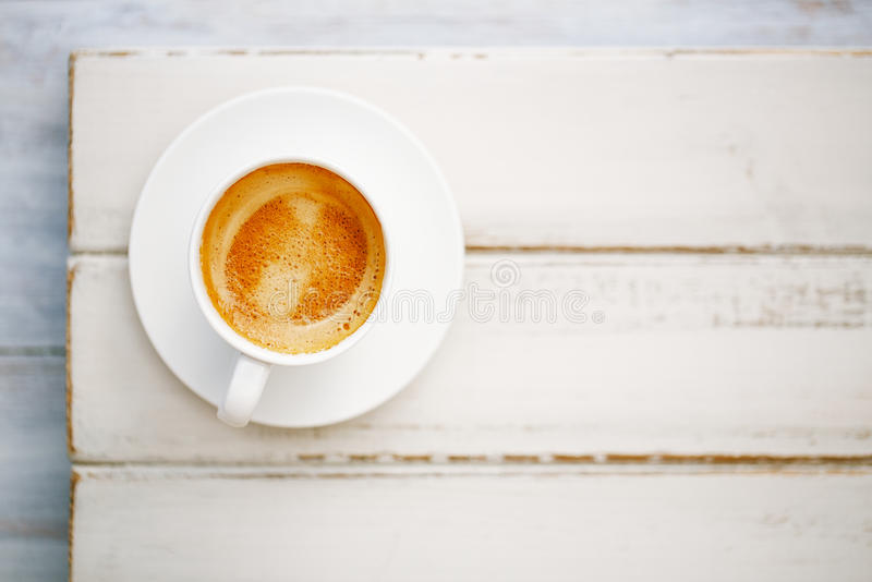 Espresso coffee in white cup on old rustic style table royalty free stock photography