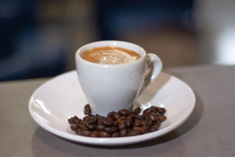 Espresso coffee in a white cup and roasted coffee beans on a saucer on wooden desk in a bar stock images
