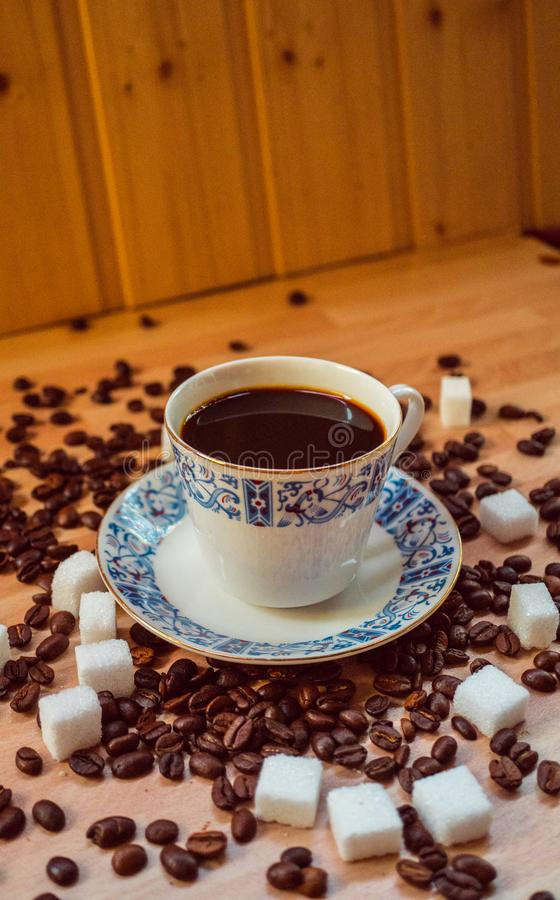 Espresso cup on the table with coffee beans and sugar cubes. Mug stock image
