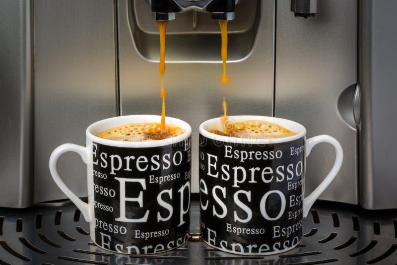 Espresso cups. Two espresso cups filled by an automatic espresso machine stock photo