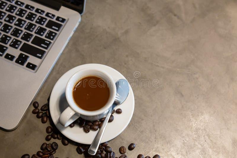 Espresso in een kop van hete koffie en koffiebonen, werkplaats in een koffiewinkel, een kop van koffie naast een laptop computer  stock fotografie