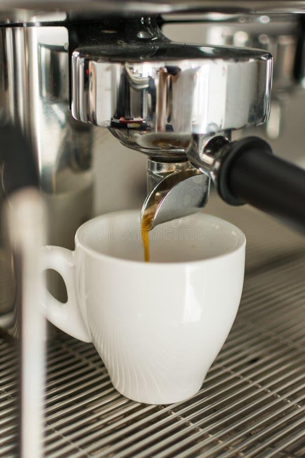 Espresso het gieten van koffiemachine in één kop stock fotografie