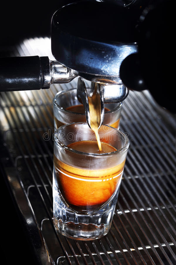 Espresso machine brewing a coffee. Coffee pouring into shot glasses royalty free stock photography