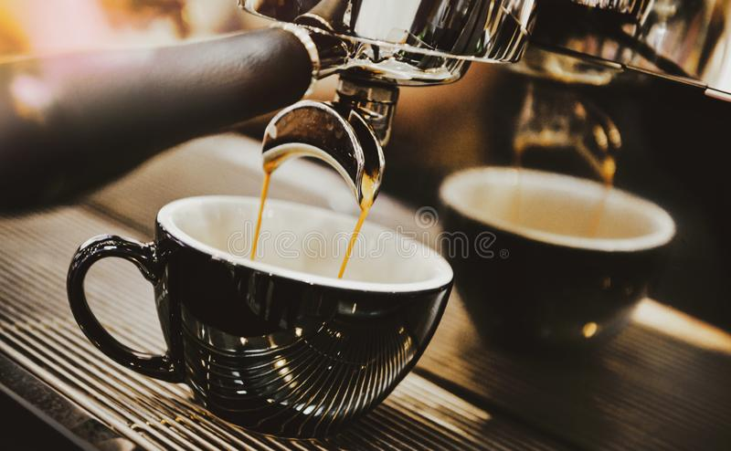 Espresso machine brewing a coffee. Coffee pouring into glasses in coffee shop, espresso pouring from coffee machine stock photo