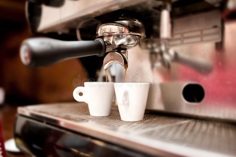Espresso machine pouring coffee in cups stock photos