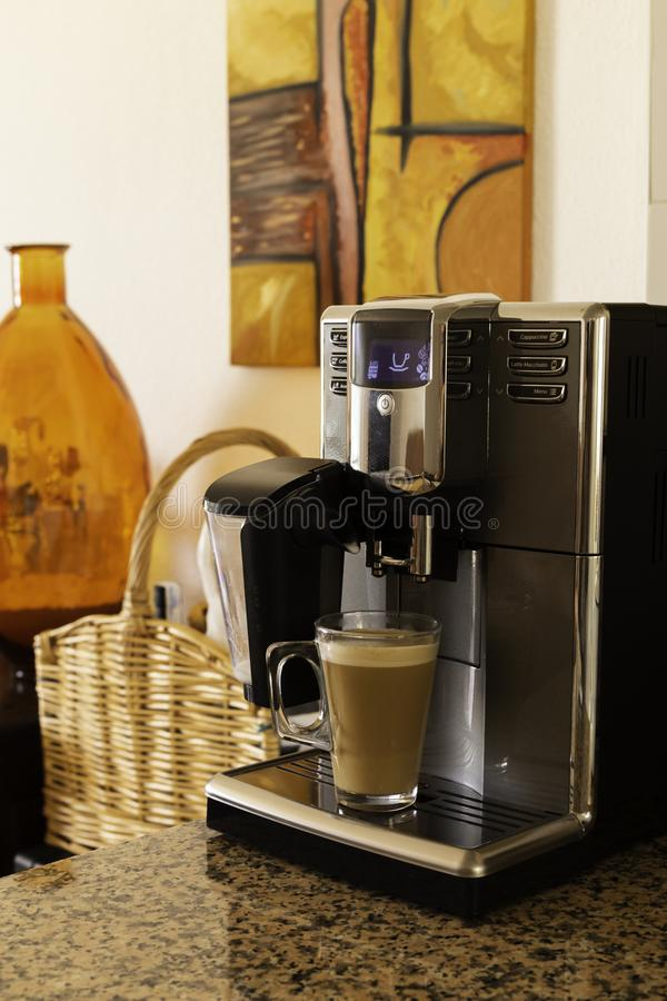 Espresso machine pours fresh cappuccino coffee close-up.  royalty free stock photo