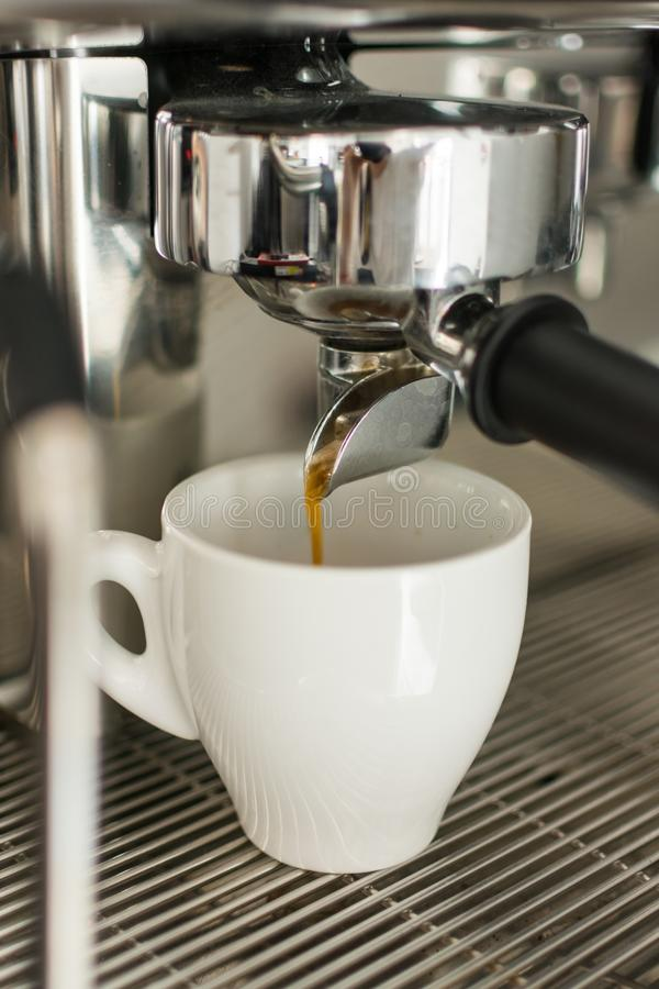 Espresso pouring from coffee machine into one cup stock photography