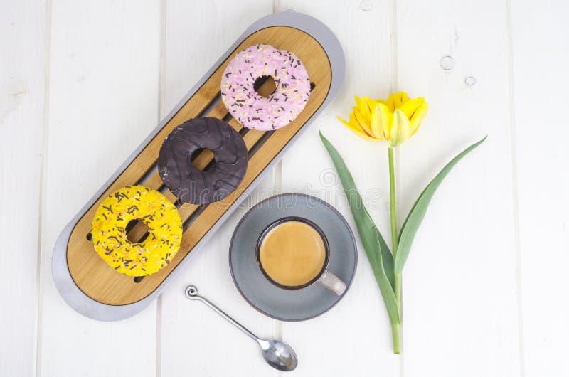 Espresso söta donuts med färgrik isläggning royaltyfri foto