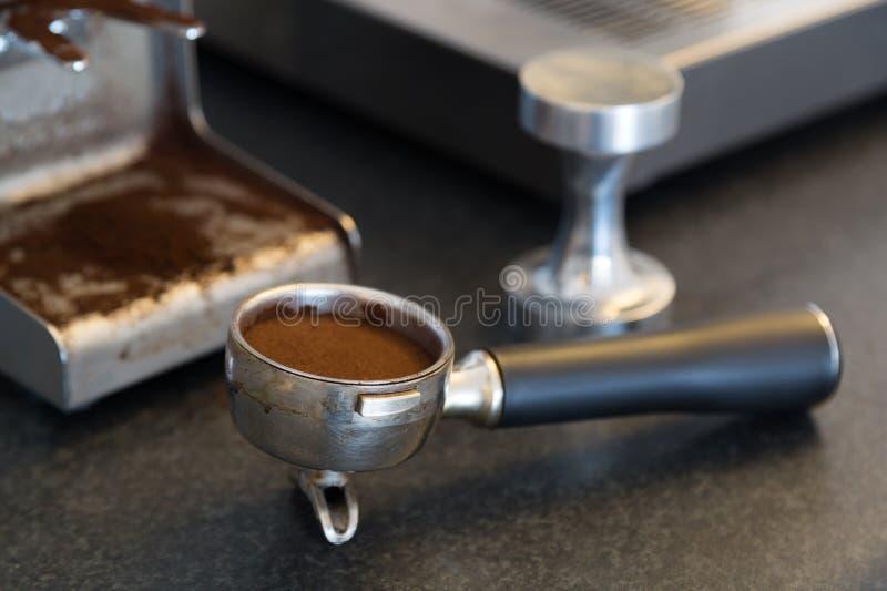Espresso tools. Espresso bayonet, also called piston or portafilter, tamper grinder and espresso machine. Shallow D.O.F royalty free stock photo