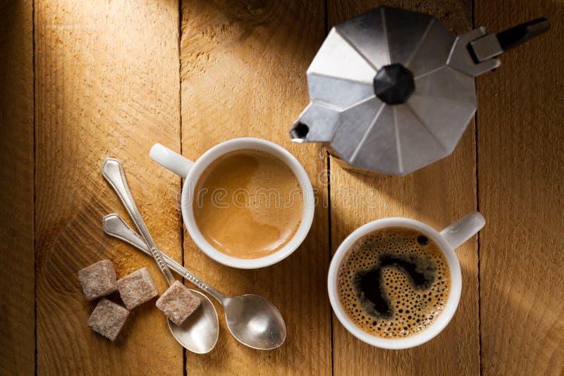 Espresso twee en een koffiezetapparaat op een ruwe houten lijst stock afbeeldingen