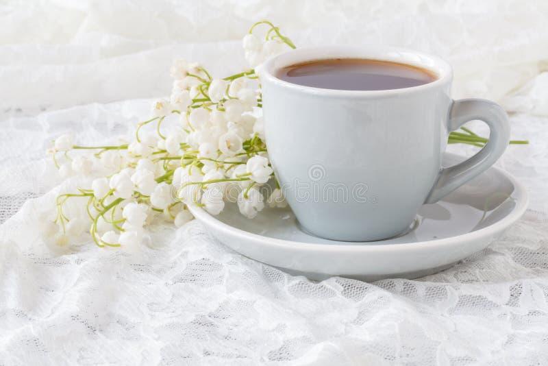 Espresso und Blumenstrauß von Blumen - Maiglöckchen lizenzfreie stockfotos