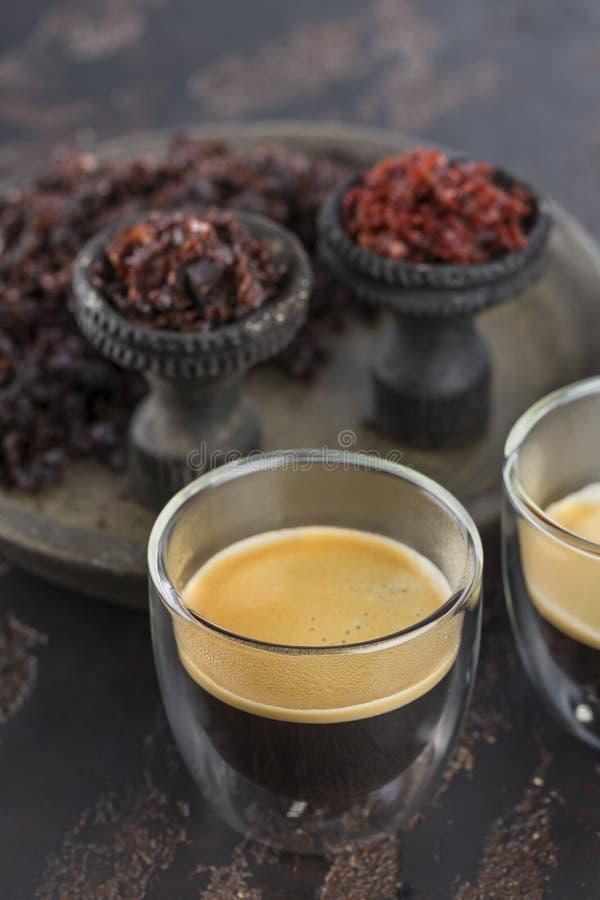 Espressokaffe i små exponeringsglaskoppar på bakgrunden av keramiska koppar för att röka vattenpipan som fylls med olika typer av fotografering för bildbyråer
