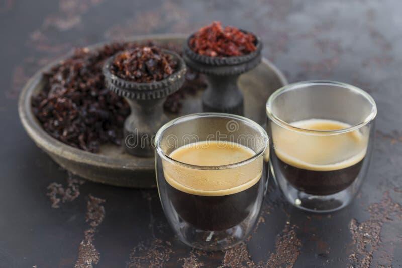 Espressokaffe i små exponeringsglaskoppar på bakgrunden av keramiska koppar för att röka vattenpipan som fylls med olika typer av royaltyfri fotografi