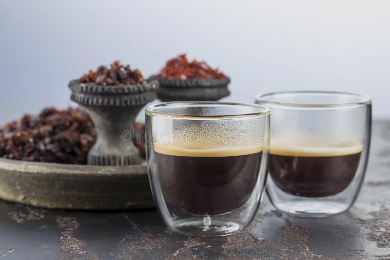 Espressokaffe i små exponeringsglaskoppar på bakgrunden av keramiska koppar för att röka vattenpipan som fylls med olika typer av arkivfoto