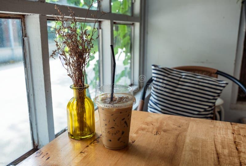 Espressokaffee im Plastikglas mit trockener Blume lizenzfreie stockbilder