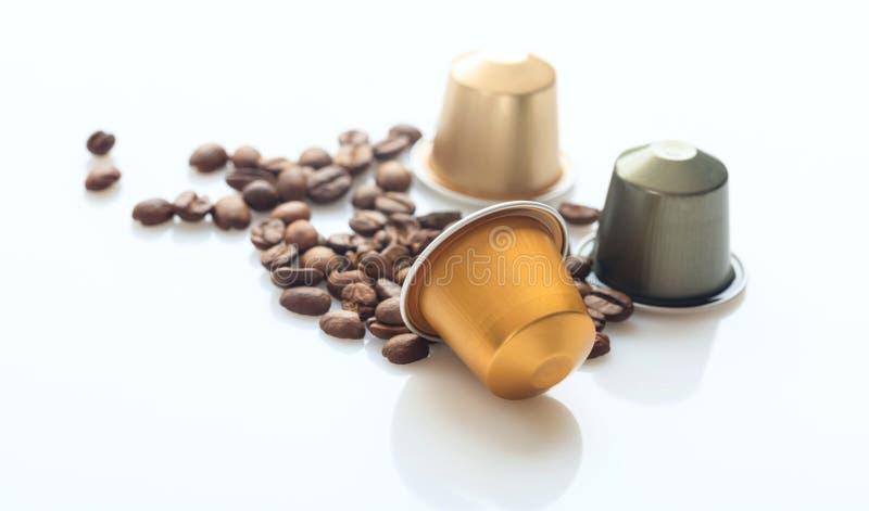Espressokaffefröskidor och kaffebönor på vit bakgrund, Closeupsikt med detaljer royaltyfri foto