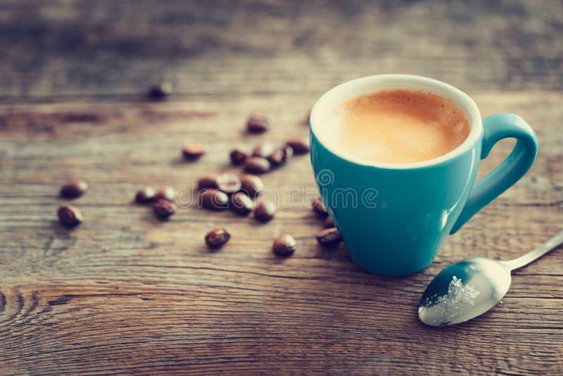 Espressokaffekopp med bönor på träbräde arkivfoto