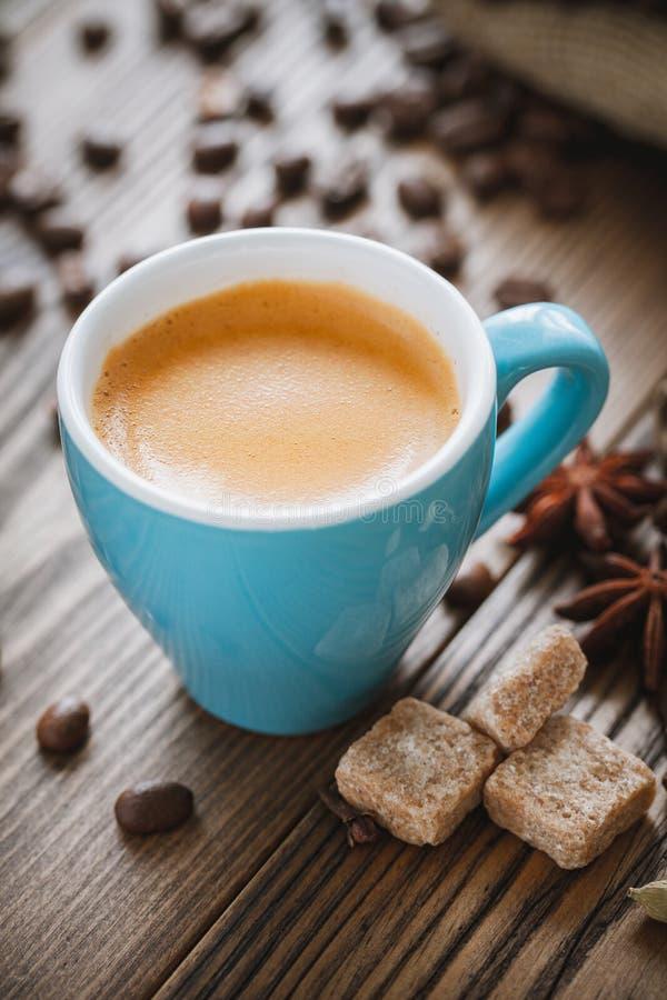 Espressokaffekopp, sockerkuber, kaffebönor och kryddor på träskrivbordet arkivfoton