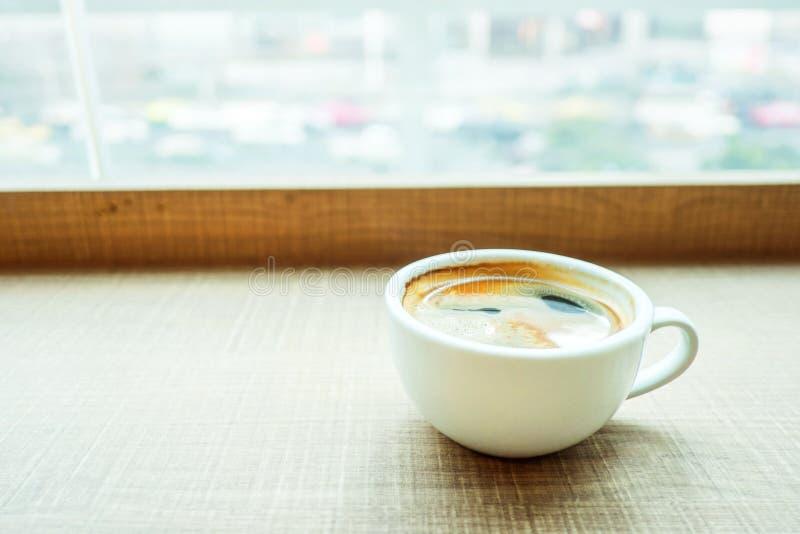 Espressokop op houten lijst in koffie met het verkeer van de onduidelijk beeldstad royalty-vrije stock foto