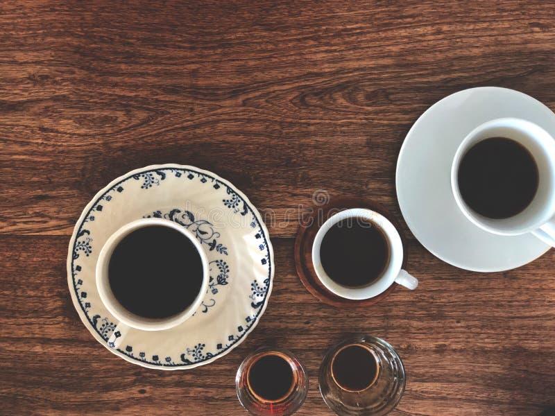 Espressoschussschale und schwarzer Kaffee auf weißer Schale auf Holztisch stockfotografie