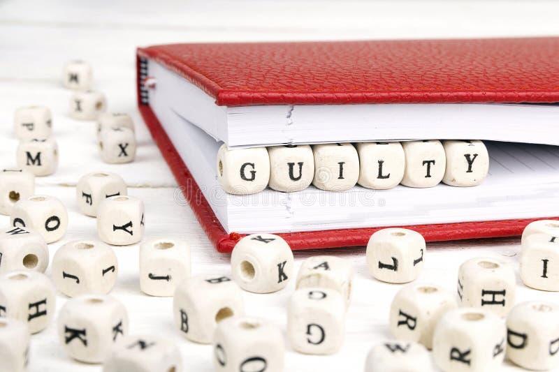 Esprima colpevole scritto in blocchi di legno in taccuino rosso sul wo bianco fotografie stock libere da diritti