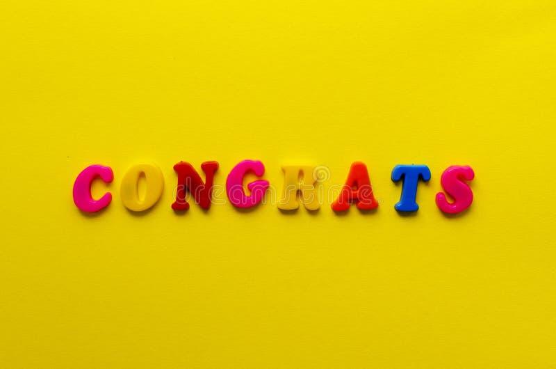 Esprima i congrats del ` dalle lettere magnetiche su fondo di carta giallo fotografia stock