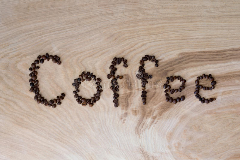 Esprima il caffè presentato dai grani su un fondo di legno immagini stock
