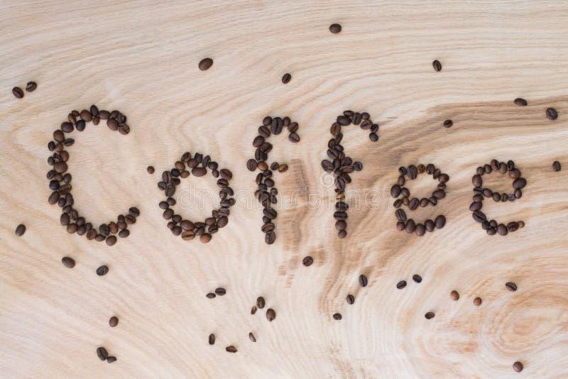 Esprima il caffè presentato dai grani su un fondo di legno immagine stock libera da diritti