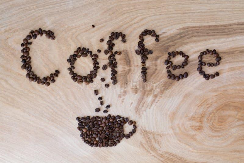Esprima il caffè presentato dai grani su un fondo di legno fotografie stock