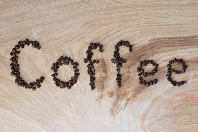Esprima il caffè presentato dai grani su un fondo di legno fotografia stock