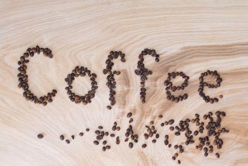 Esprima il caffè presentato dai grani su un fondo di legno fotografia stock libera da diritti