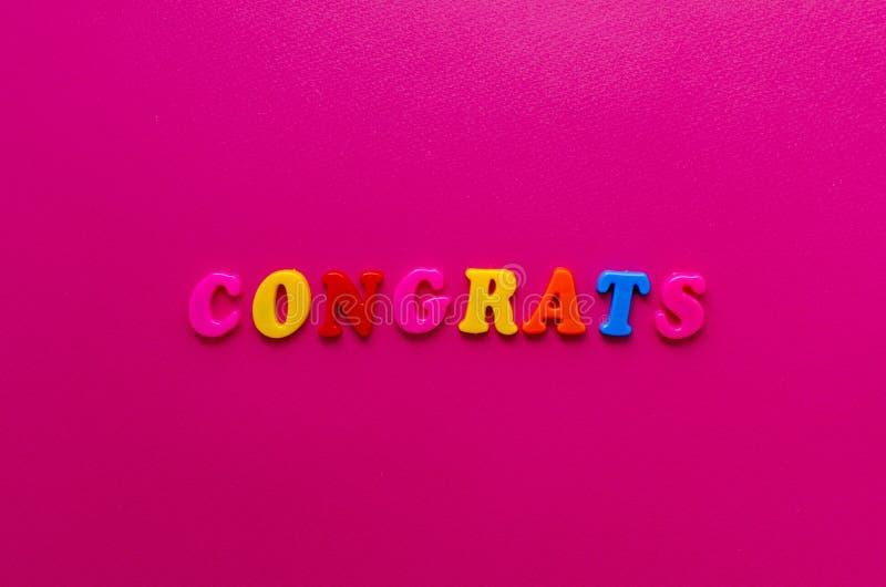 Esprima il ` dei congrats del ` dalle lettere magnetiche su fondo di carta rosa fotografia stock