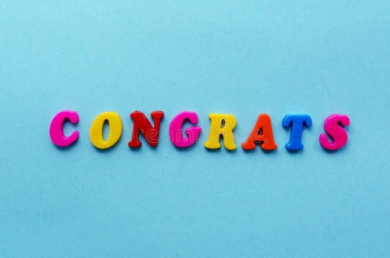 Esprima il ` dei congrats del ` dalle lettere magnetiche sul fondo della carta blu immagini stock