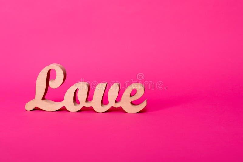 Esprima l'amore, lettere di legno su carta rosa con spazio per testo Fondo di giorno del ` s del biglietto di S Lovestory o decor immagini stock libere da diritti