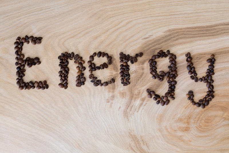 Esprima l'energia presentata dai chicchi di caffè su un fondo di legno fotografia stock