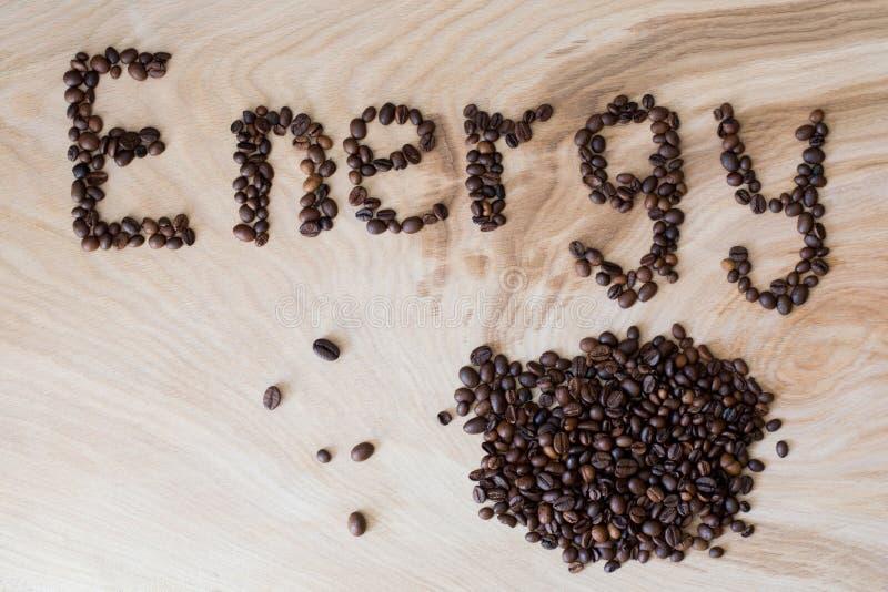 Esprima l'energia presentata dai chicchi di caffè su un fondo di legno immagine stock