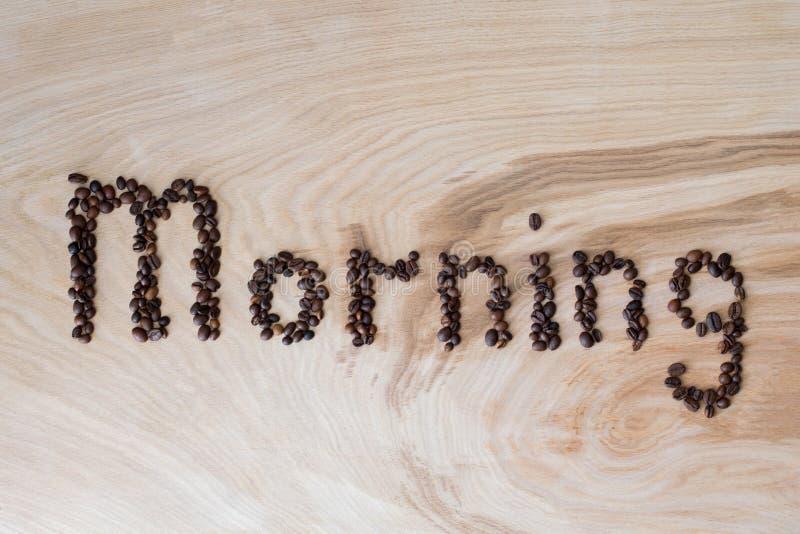 Esprima la mattina presentata dai chicchi di caffè su un fondo di legno fotografia stock libera da diritti
