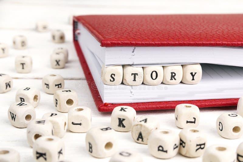 Esprima la storia scritta in blocchi di legno in taccuino rosso su bianco corteggiano fotografie stock libere da diritti