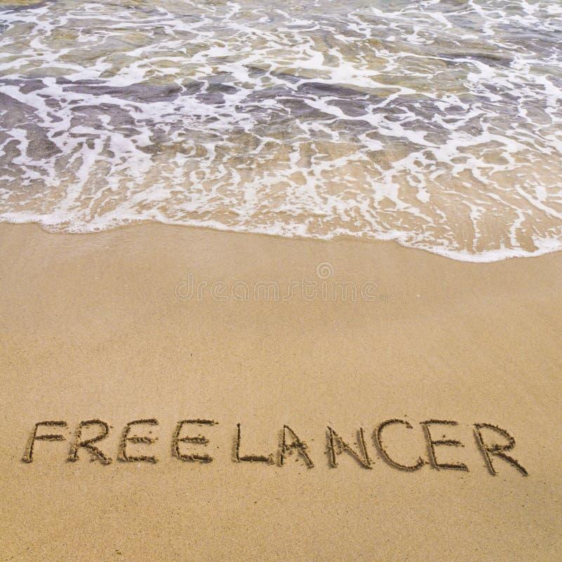 Esprima le FREE LANCE scritte in sabbia, su una bella spiaggia fotografie stock