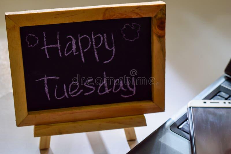 Esprima martedì felice scritto su una lavagna e sullo smartphone, computer portatile fotografia stock libera da diritti