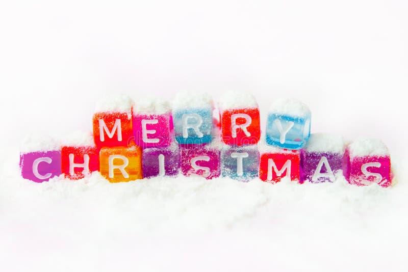 esprime il Buon Natale fatto dei blocchetti variopinti delle lettere sul fondo bianco della neve Disposizione piana, vista superi immagini stock libere da diritti