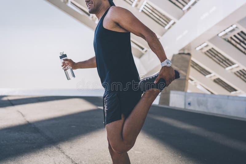 Esprinter de sexo masculino muscular del atleta que hace estirando el ejercicio, ejercitando al aire libre, activando afuera Form imagenes de archivo