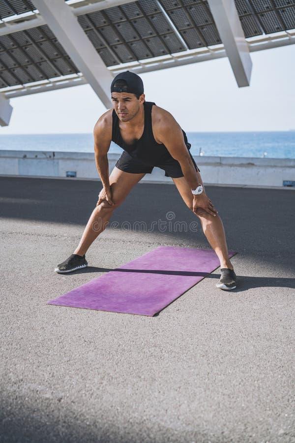 Esprinter de sexo masculino muscular del atleta que hace estirando el ejercicio, ejercitando al aire libre, activando afuera Form fotos de archivo libres de regalías