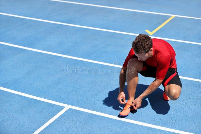 Esprinter del atleta que consigue listo para correr atar encima de cordones de zapato en pistas de funcionamiento del estadio Cor fotografía de archivo